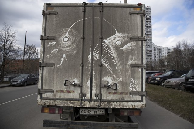 """In this photo taken on Saturday, April 22, 2017, a drawing of an angler is made on a muddy back of a truck by artist Nikita Golubev in Moscow, Russia. The grimy trucks traversing the polluted and dusty streets of Moscow have inspired a new kind of street art in Russia's capital. When Nikita Golubev sees a dirty white truck or van he uses it as a canvas for his drawings. With his gloved hand, he draws giant pigeons on the back of a delivery truck. A face with reptilian eyes appears on the back of a white van covered in enough dirt to make the license plate all but illegible. Surfers skim along the side of a truck. But none of it lasts. """"Everything is washed away with the first rain"""", Golubev says. """"It goes away and nothing remains"""". His creations are preserved only in the photographs he takes and posts on Instagram, where they have acquired a following. He signs his drawings Pro Boy Nick. Golubev thinks people like his drawings because they are impermanent. """"It's art just for fun"""", he says. (Photo by Pavel Golovkin/AP Photo)"""