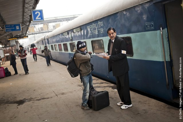 A passenger checks his seating on the Amritsar bound train, as he receives help from a conductor at the Nizamuddin Railway Station in New Delhi, India