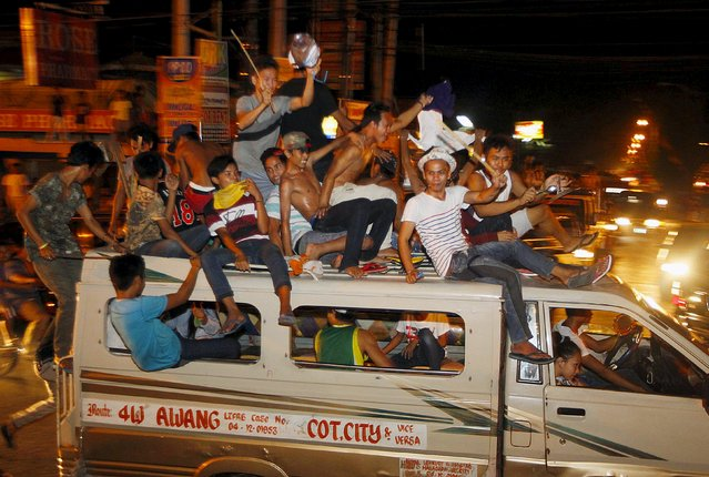Filipino Muslims ride on top of a vehicle as they celebrate the end of the holy month of Ramadan in Cotabato city, in southern Philippines, July 16, 2015. Picture taken July 16, 2015. (Photo by Marconi Navales/Reuters)