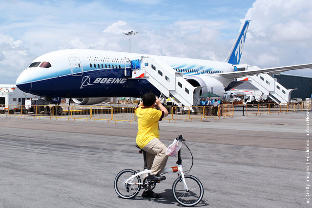 A man stops to take a photograph of the Boeing 787 Dreamliner