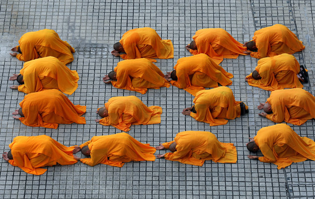 "Buddhist monks prostrate as they perform the ""three steps one bow"" ceremony at Kong Meng San Phor Kark See Monastery on the eve of Vesak Day in Singapore May 9, 2017. (Photo by Edgar Su/Reuters)"