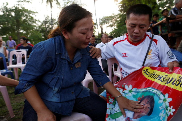 Yupin Saw-wa, (L) cries as she holds a picture of her daughter, who died after a fire swept through the Christian Pitakiatwittaya School in the northern province of Chiang Rai, Thailand, May 23, 2016. (Photo by Athit Perawongmetha/Reuters)