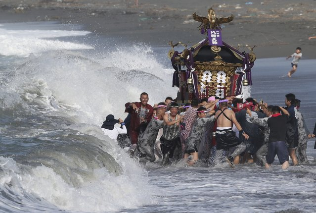 Participants carry a portable shrine, or mikoshi, into the sea during a purification rite at the annual Hamaori Festival in Chigasaki, west of Tokyo early Monday, July 20, 2015. (Photo by Koji Sasahara/AP Photo)