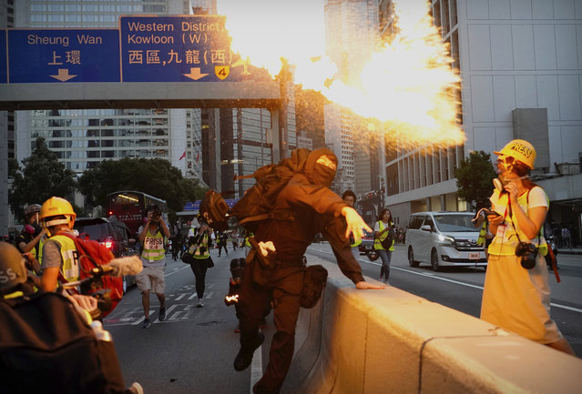 A demonstrator hurls a firebomb during a protest in Hong Kong, Saturday, November 2, 2019. Anti-government protesters attacked the Hong Kong office of China's official Xinhua News Agency for the first time Saturday after chaos broke out downtown, with police and demonstrators trading gasoline bombs and tear gas as the protest movement approached the five-month mark. (Photo by Vincent Yu/AP Photo)