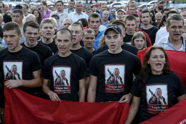 "Members of the far-right radical group Right Sector and their supporters shout slogans as they attend an anti-government rally in Kiev, Ukraine, July 21, 2015. The inscription on the t-shirt reads ""God with us, and a Kalashnikov machine gun"". (Photo by Gleb Garanich/Reuters)"