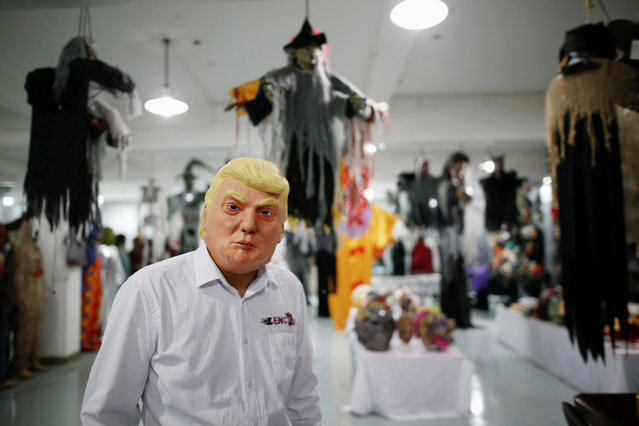 The manager of Jinhua Partytime Latex Art and Crafts Factory wearing a mask of U.S. Republican presidential candidate Donald Trump poses as he presents products to reporters at his factory's showroom in Jinhua, Zhejiang Province, China, May 25, 2016. (Photo by Aly Song/Reuters)