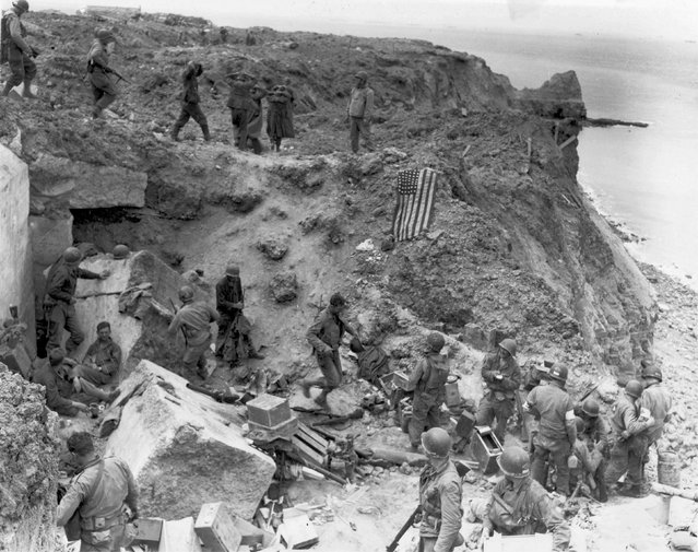 A U.S. flag lies as a marker on a destroyed bunker two days after the strategic site overlooking D-Day beaches was captured by U.S. Army Rangers at Pointe du Hoc, France, June 8, 1944. REUTERS/US National Archives