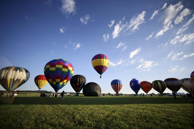 Inflated hot air balloons begin lifting off during the 33rd annual QuickChek New Jersey Festival of Ballooning at Solberg Airport Friday, July 24, 2015, in Readington, N.J. (Photo by Mel Evans/AP Photo)