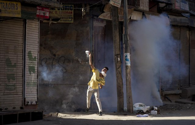 A Kashmiri Muslim protester throws back an exploded tear gas shell at Indian police during a protest amid strike in Srinagar, Indian controlled Kashmir, Saturday, July 25, 2015. Shops, businesses and schools are shut in Indian-controlled Kashmir after a strike called by traders' organization and separatist groups against alleged burning of a flag bearing Islamic verses in Rajouri district, according to local news reports. (Photo by Dar Yasin/AP Photo)