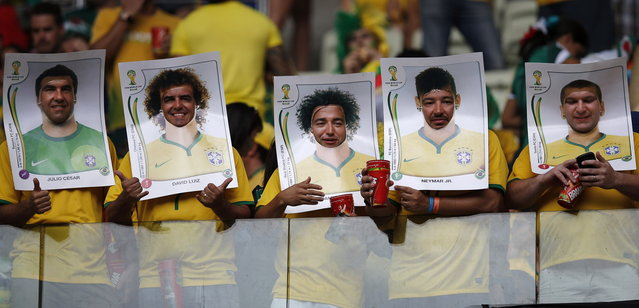 Brazilian fans wear cut out poster of Brazil national players before the group A World Cup soccer match between Brazil and Mexico at the Arena Castelao in Fortaleza, Brazil, Tuesday, June 17, 2014. (Photo by Eduardo Verdugo/AP Photo)