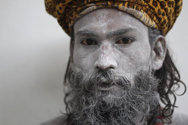 An Indian Hindu holy man who has his face smeared with ash looks at the camera during the Ambubasi festival at the Kamakhya Hindu temple in Gauhati, India, Sunday, June 22, 2014. The annual festival where hundreds of holy men from an esoteric form of Hinduism, gather to perform rituals at the temple begins on June 22. (Photo by Anupam Nath/AP Photo)