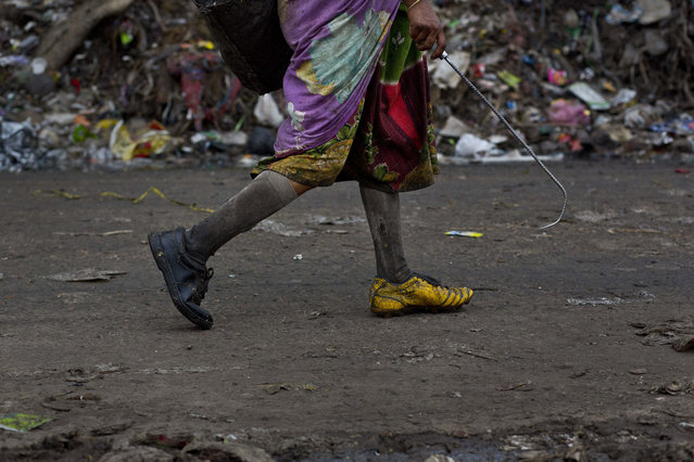In this Monday, June 5, 2017, file photo, an Indian woman walks as se searches for recyclable materials at a garbage dumping site on the outskirts of Gauhati, Assam state, India. (Photo by Anupam Nath/AP Photo)