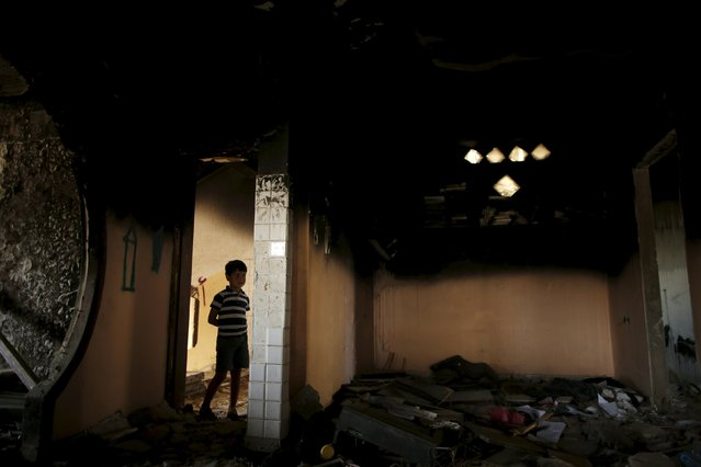 A Palestinian boy looks on as he stands inside his family's house that witnesses said was badly damaged and burnt by Israeli shelling during a 50-day war last summer, in the east of Gaza City May 6, 2015. (Photo by Mohammed Salem/Reuters)