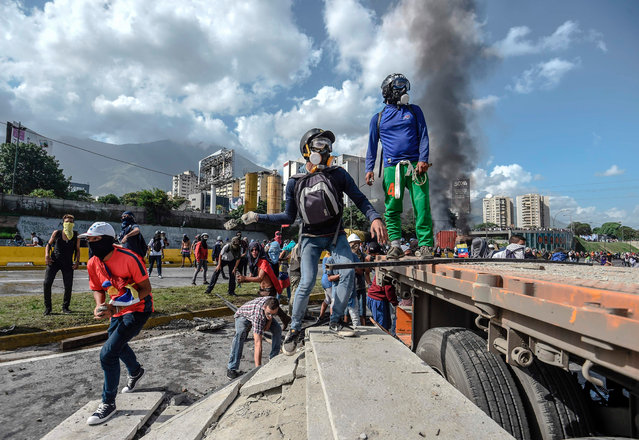 Opposition activists blocking a highway in Caracas clash with the police during a protest against the government of President Nicolas Maduro, on June 23, 2017. Near- daily protests against President Nicolas Maduro, blamed for an economic crisis that has caused desperate shortages of food, medicine and other basic goods, began on April 1, with demonstrators demanding his removal and the holding of new elections. The demonstrations have often turned violent with 75 people killed and more than 1,000 injured so far, prosecutors say, and more than 3,000 arrested, according to the NGO Forum Penal. (Photo by Juan Barreto/AFP Photo)