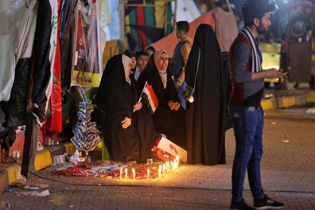 Women light candles for protesters who have been killed in demonstrations during ongoing anti-government protests, in Najaf, Iraq, Tuesday, December 31, 2019. (Photo by Anmar Khalil/AP Photo)