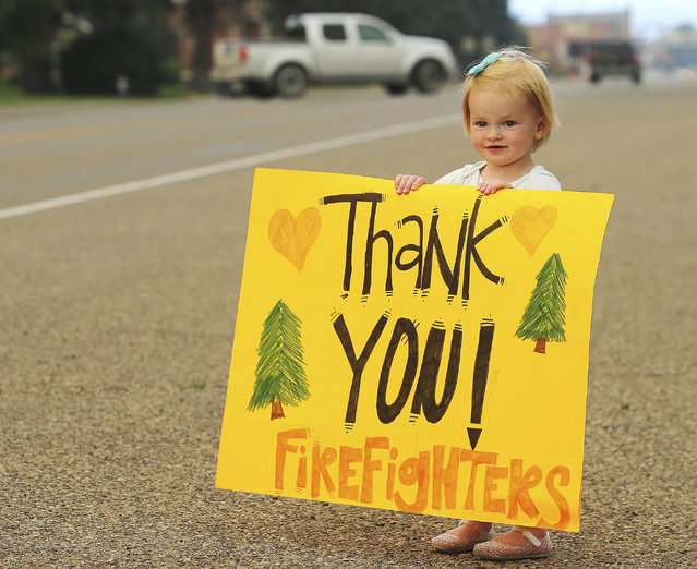 Kylie Walter holds a sign as she and other kids wait for fire crews to return from fighting a wildfire near the ski town of Brian Head near the town of Panguitch, Utah, Tuesday, June 27, 2017. (Photo by Scott G Winterton/The Deseret News via AP Photo)