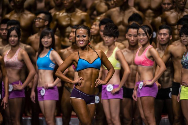 Bodybuilders flexe muscles for judges on stage during the Hong Kong Bodybuilding Championship on June 29, 2014  at the Queen Elizabeth Stadium in Hong Kong, Hong Kong. (Photo by Victor Fraile/Getty Images)