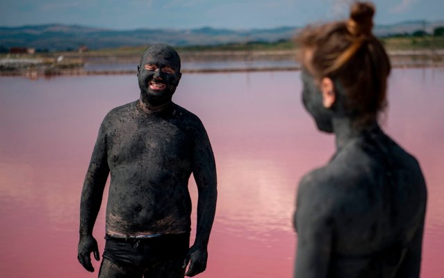 A couple covered in mud wait for it to dry at the Salt-works lakes near the Black Sea town of Burgas in Bulgaria on July 25, 2019. Thousands of tourists visit the red salt lakes for mud baths, which are believed to help the healing of muscular disorders and rheumatism. (Photo by Nikolay Doychinov/AFP Photo)