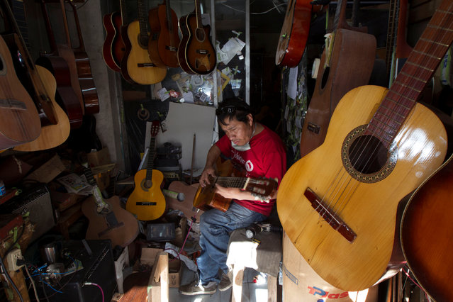 Ecuadorian luthier Ivan Ibujes plays a guitar after repairing it at his shop in Quito, June 17, 2016. (Photo by Guillermo Granja/Reuters)