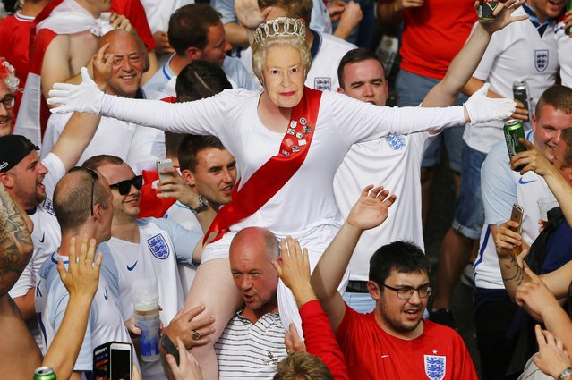 Football Soccer, EURO 2016, Saint Etienne, France on June 20, 2016. An female England fan wears a mask of Queen Elizabeth II as she rides on the shoulders of her mates gathering in Saint Etienne ahead of their team's match against Slovakia. (Photo by Wolfgang Rattay/Reuters)