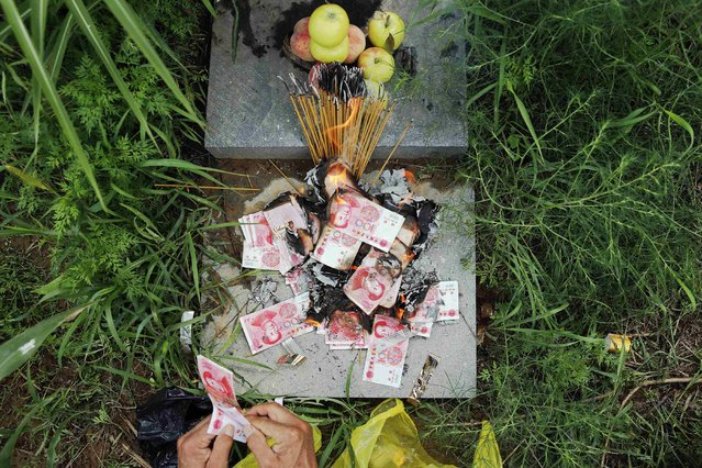 """Zhang Shuangbing, the independent researcher about Chinese """"comfort women"""" during World War Two, burns incense sticks and fake money after bringing reporters to the tomb of Liu Mianhuan at a mountain in Xipan village, Shanxi Province, China, July 18, 2015. (Photo by Kim Kyung-Hoon/Reuters)"""