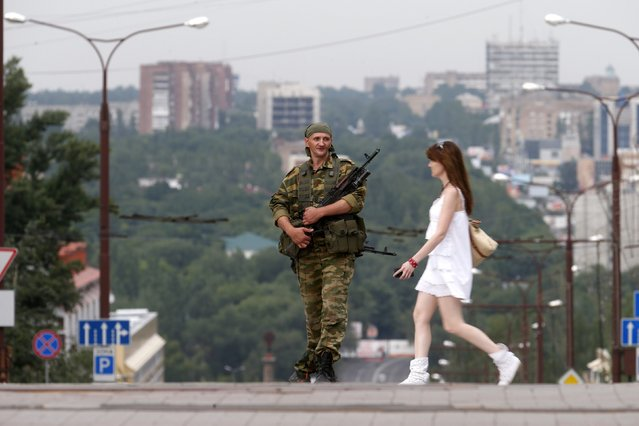 A pro-Russian separatist stands guard nearby a rally in support of Novorossiya (New Russia) on Lenin Square in the center of the eastern Ukrainian city of Donetsk, on Jule 13, 2014. (Photo by Maxim Zmeyev/Reuters)