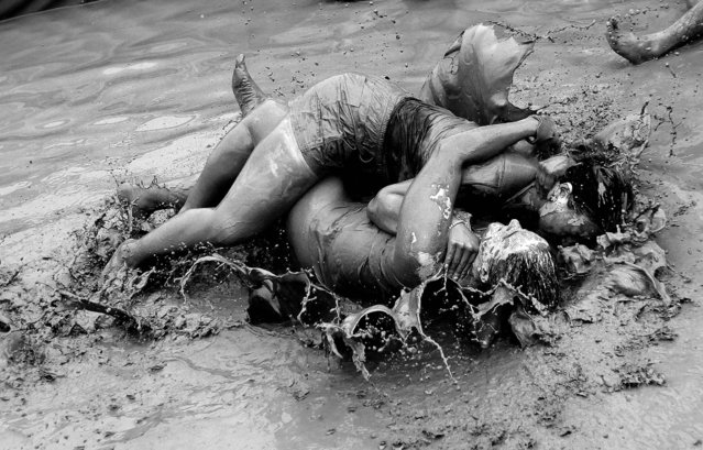 Women wrestle in a mud pool during the Boryeong Mud Festival. (Photo by Ahn Young-joon/Associated Press)