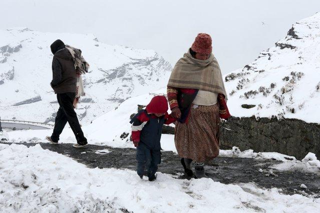 People walk in snow in La Cumbre, near La Paz, Bolivia August 12, 2015. (Photo by David Mercado/Reuters)