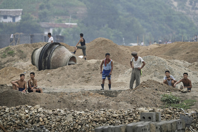 In this Friday, July 21, 2017, photo, men and boys rest at a construction site on the outskirts of Hamhung, North Korea's second-largest city, where construction workers unearthed a rusted but still potentially deadly mortar round in February. North Korea is just one of many countries still dealing with the explosive legacy of major wars. But the three-year Korean War, which ended in what was supposed to be a temporary armistice on July 27, 1953, was one of the most brutal ever fought. (Photo by Wong Maye-E/AP Photo)