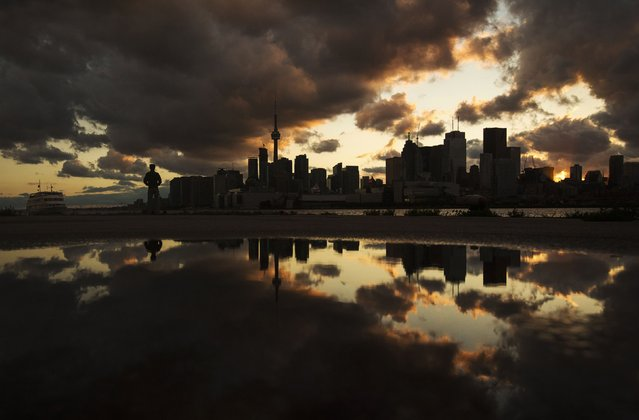 A man stands in front of the skyline after a rainy day in Toronto, July 8, 2014. (Photo by Mark Blinch/Reuters)