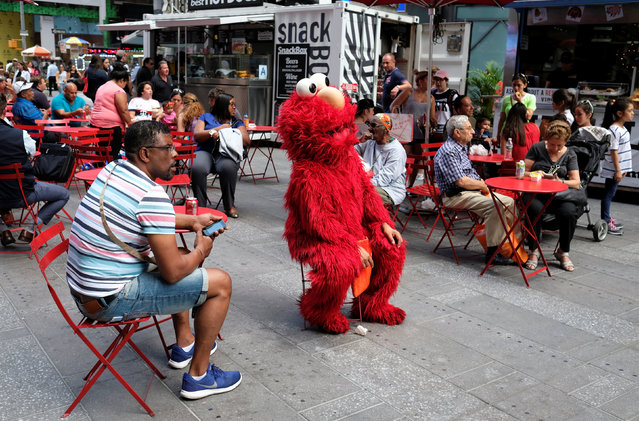 A person dressed up as Sesame Street's Elmo takes a break from charging tourists to photograph themselves with him, at a pedestrian walkway on Times Square, in Manhattan borough of New York City, U.S., June 29, 2016. Picture taken June 29, 2016. (Photo by Rickey Rogers/Reuters)