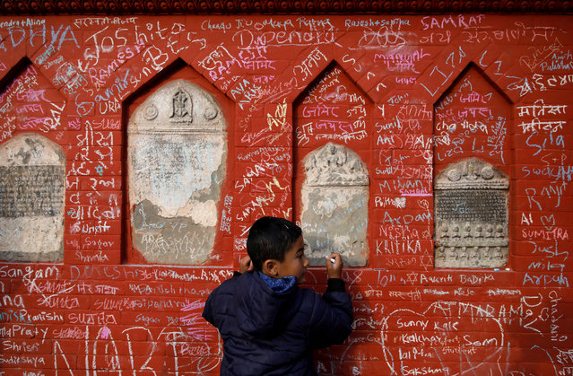 A boy writes on the wall of a Saraswati temple during the Shreepanchami festival dedicated to goddess of education Saraswati in belief that the goddess will help devotees excel in education, in Kathmandu, Nepal on January 30, 2020. (Photo by Navesh Chitrakar/Reuters)