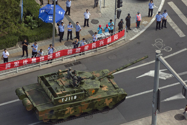 A Chinese battle tank leaves after rehearsals ahead of the Sept. 3 military parade to commemorate the end of World War II in Beijing, Sunday, August 23, 2015. (Photo by Ng Han Guan/AP Photo)