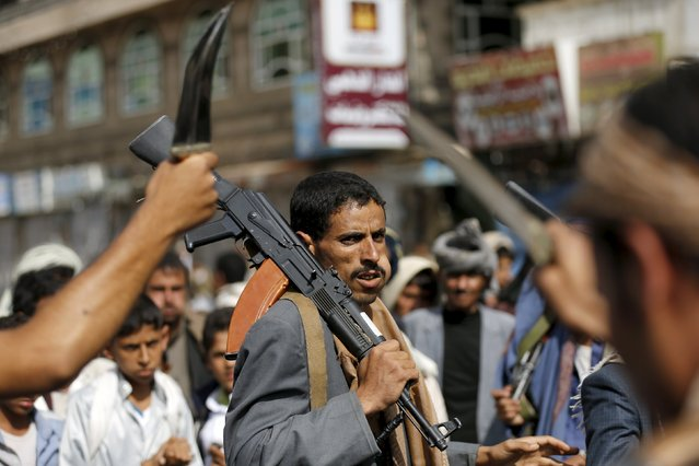 A Houthi follower carries his rifle as he dances with others the traditional Baraa dance ahead of a demonstration against the Saudi-led air strikes in Yemen's capital Sanaa August 24, 2015. (Photo by Khaled Abdullah/Reuters)
