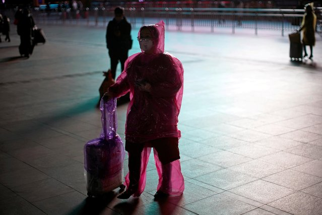 A woman wears a face mask and plastic raincoat as a protection from coronavirus at Shanghai railway station, in Shanghai, China on February 17, 2020. (Photo by Aly Song/Reuters)