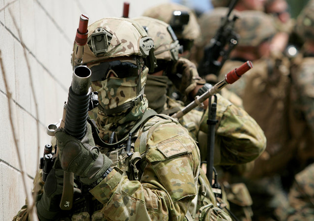 Australian Army soldiers with the 2RAR prepare to breach a building during a helicopter insertion exercise with U.S. Marines in the Kahuku mountains training area during the multi-national military exercise RIMPAC in Honolulu, Hawaii, July 13, 2016. (Photo by Hugh Gentry/Reuters)