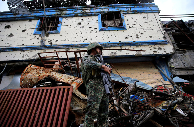 A government soldier stands on guard in front of damaged buildings and houses as troops continue their assault on its 105th day of clearing operations against pro-IS militants who have seized control of large parts of Marawi City, Philippines September 4, 2017. (Photo by Romeo Ranoco/Reuters)