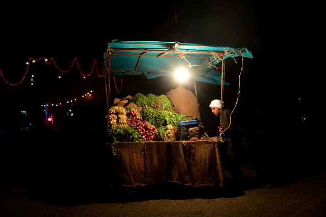 In this photograph taken on July 26, 2016, an Afghan fruit vendor waits for customers at a roadside stall in Herat. (Photo by Aref Karimi/AFP Photo)