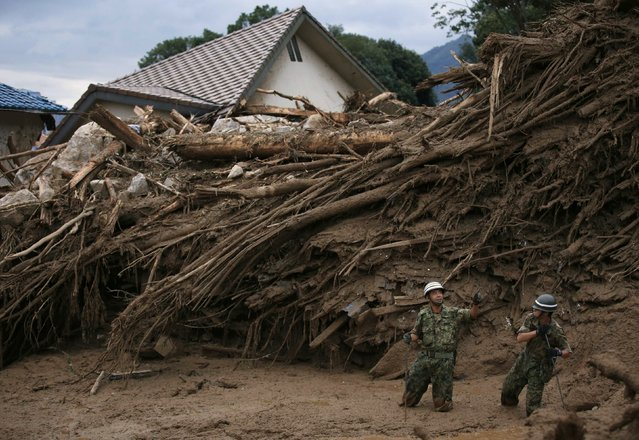 Japan Self-Defense Force (JSDF) soldiers search for survivors at a site where a landslide swept through a residential area at Asaminami ward in Hiroshima, western Japan, August 20, 2014. At least 36 people, including several children, were killed in Japan on Wednesday, when landslides triggered by torrential rain slammed into the outskirts of the western city of Hiroshima, and the toll could rise further, police said. (Photo by Toru Hanai/Reuters)