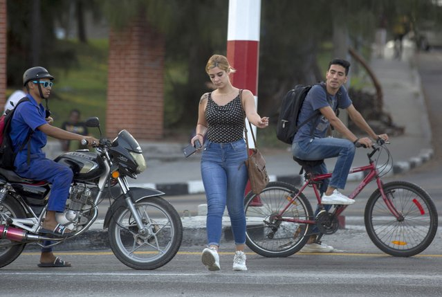 In this December 9, 2019 photo, a woman crosses a street as a young man on a bicycle stares at her in Havana, Cuba. For 60 years, Cuba's communist government has monopolized virtually every aspect of life on the island, but this year one aspect of that state monopoly has begun to loosen, and as 2019 comes to a close one of the most important of those new civil society causes is women's rights. (Photo by Ismael Francisco/AP Photo)