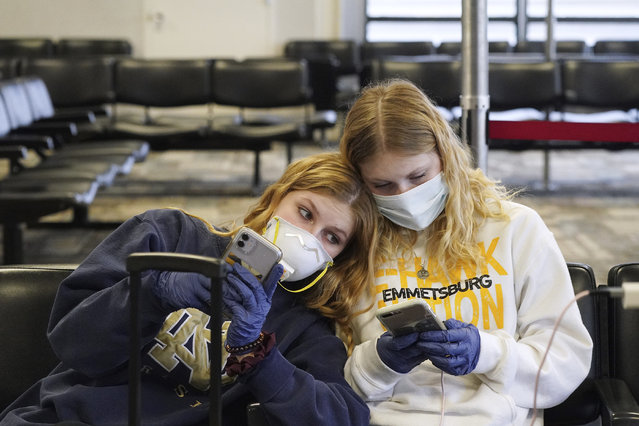 Rachel Miner, 15, left, of Emmetsburg, Iowa, sits with Carlotta Haas, 15, a foreign exchange student from Duesseldorf, Germany, who had been living with Miner and her family but was called home, as they waited for her flight Wednesday, March 25, 2020, in at Minneapolis-St. Paul International Airport in Minneapolis. (Photo by Anthony Souffle/Star Tribune via AP Photo)