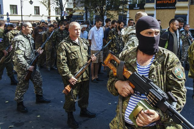 Pro-Russian gunmen guard parade dozens of captured Ukrainian soldiers during a march in mockery of the country's Independence Day celebrations in the main separatist stronghold Donetsk on August 24, 2014. (Photo by Alexandr Osinskiy/AFP Photo)