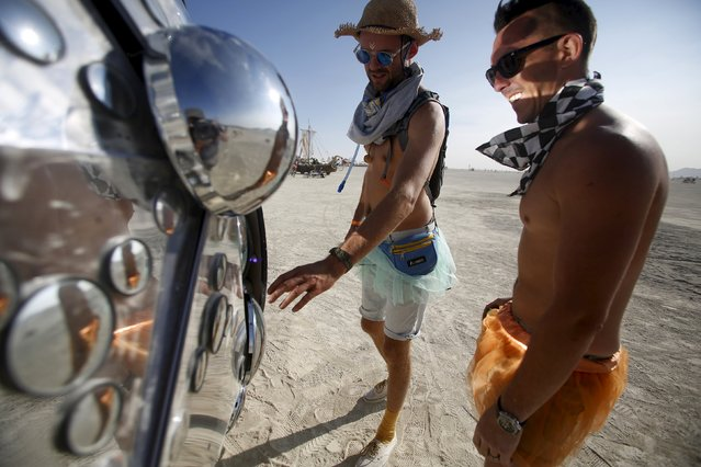 """Dan Landers (L) and Tom Kelshaw interact with the art installation Compound Eye during the Burning Man 2015 """"Carnival of Mirrors"""" arts and music festival in the Black Rock Desert of Nevada, August 31, 2015. (Photo by Jim Urquhart/Reuters)"""