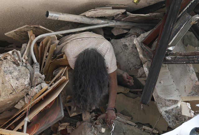 The body of woman hangs crushed by a collapsed building in the neighborhood of Roma Norte, in Mexico City, Tuesday, September 19, 2017. Throughout Mexico City, rescuer workers and residents dug through the rubble of collapsed buildings seeking survivors following a 7.1 magnitude quake. (Photo by Marco Ugarte/AP Photo)