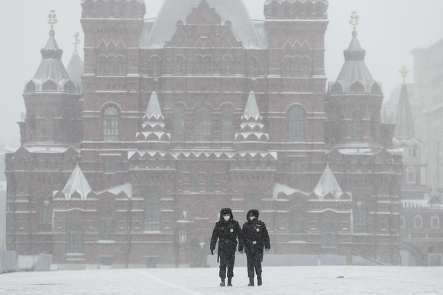 Police officers walk across an empty Red Square in Moscow, Russia, Tuesday, March 31, 2020. The Russian capital has woken up to a lockdown obliging most people in the city of 13 million to stay home. The government ordered other regions of the vast country to quickly prepare for the same as Moscow, to stem the spread of the new coronavirus. (Photo by Pavel Golovkin/AP Photo)