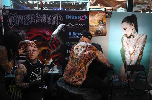 A tattoo artist works on a man's back during the London Tattoo Convention at the Tobacco Docks, in London, Britain, 24 September 2017. (Photo by Facundo Arrizabalaga/EPA/EFE)