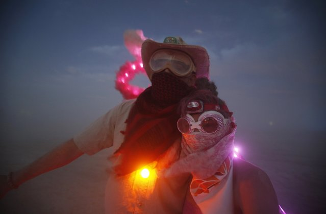 "Wade Harrell (L) and his wife Heather Harrell geared up for the dust during the Burning Man 2014 ""Caravansary"" arts and music festival in the Black Rock Desert of Nevada, August 29, 2014. (Photo by Jim Urquhart/Reuters)"