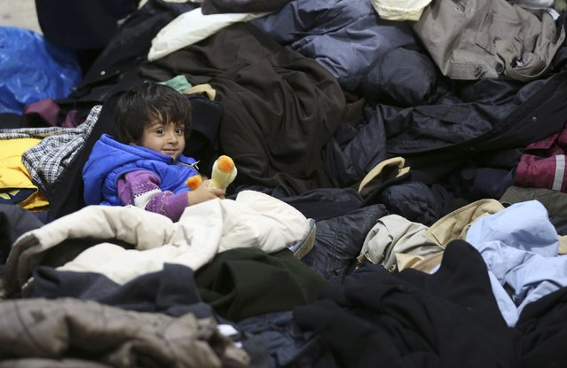 A child sits among clothes at a distribution centre with donated articles for daily use after arriving with a train in Dortmund, Germany September 6, 2015. (Photo by Ina Fassbender/Reuters)