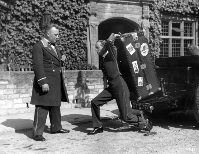 """Actor H. B. Warner (1875–1958) struggles with a heavy trunk while Wally Patch looks on, in the """"talkie"""" remake of the United Artists' film """"Sorrell and Son"""", 1934. (Photo by Hulton Archive)"""