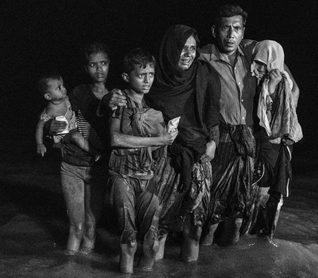 A Rohingya refugee family reacts as they disembark from a boat after arriving on the Bangladesh side of the Naf River at night from Myanmar on September 26, 2017 in Cox's Bazar, Bangladesh. (Photo by Kevin Frayer/Getty Images)